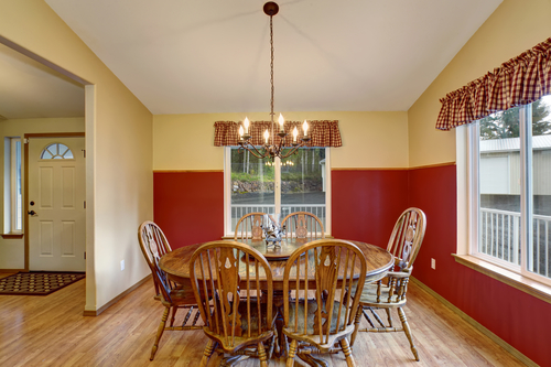 Dinning room with red and tan interior painting, also including nice table and chair set.